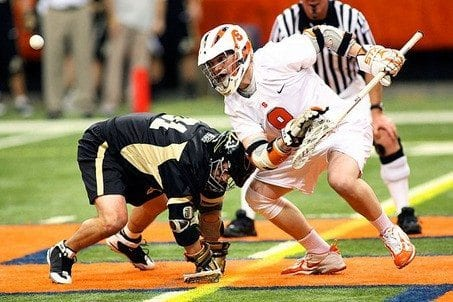 Syracuse University's Jake Moulton flipping the ball out during a faceoff with Army's Sean Reppard.